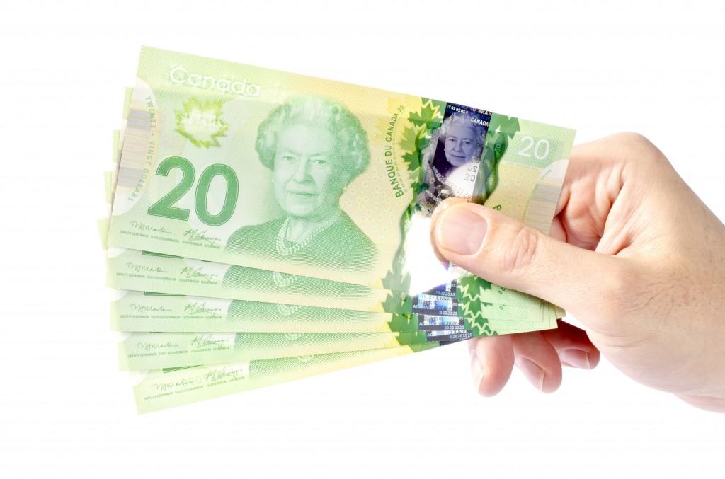 Hand Holding New Canadian Twenty Dollar Bills Isolated