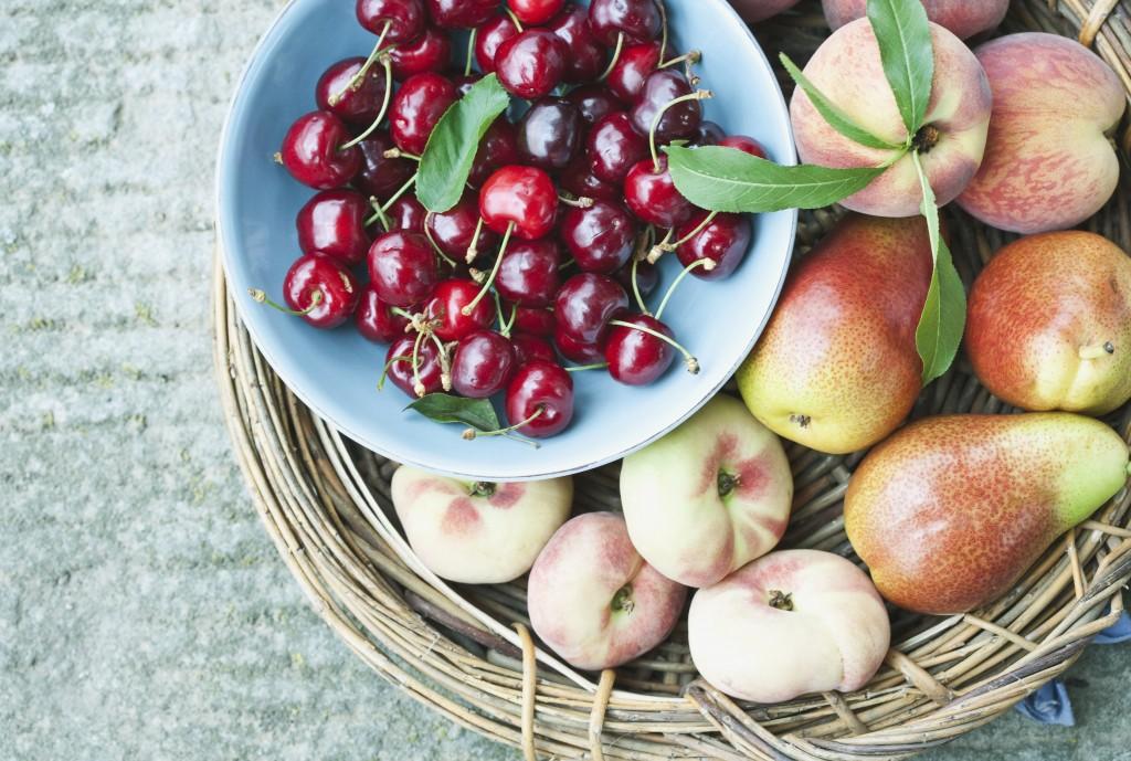Italien,Toskana,Magliano,Close up von Pfirsich und Birne im Korb mit Kirschen in der Schüssel
