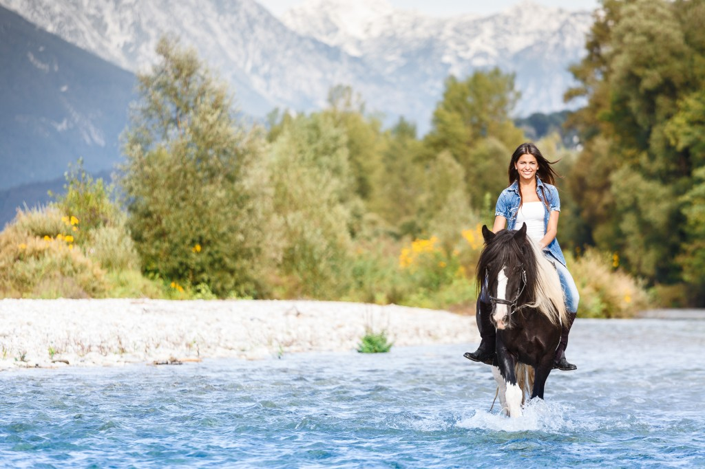 Beautiful Female horse rider crossing river in a mountainous lan