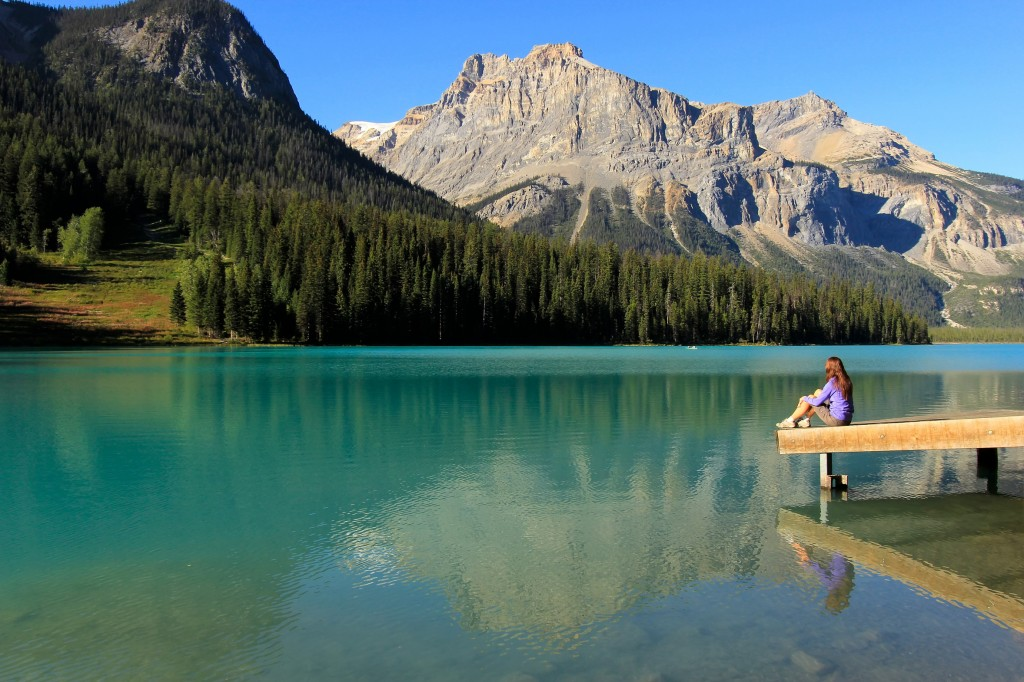 Young woman sitting on a pier at Emerald Lake, Yoho National Par