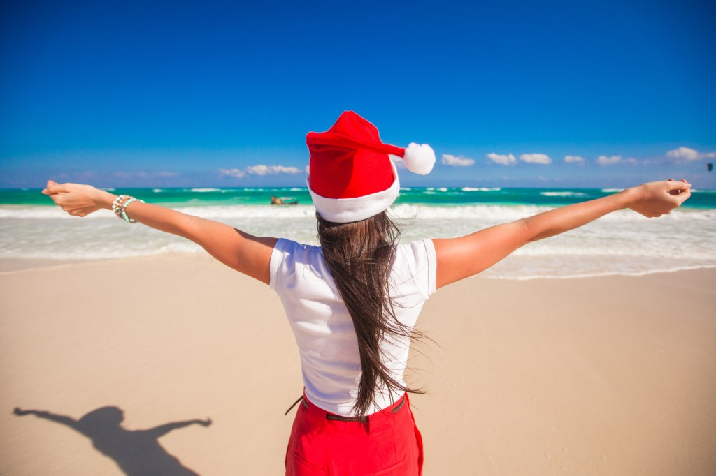 Back view of beautiful girl in Santa Hat walking spread her hands on white beach