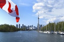 Canada flag is waving front of famous Toronto City view